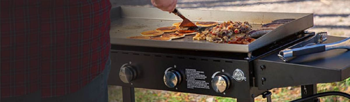 A person flips pancakes on a propane-powered griddle in a grassy area. Also on the grill are hash browns, sausages, and bacon, but there's still plenty of room.