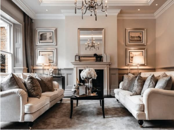 Neutral-toned sitting room with a multi-light chandelier, plush furniture, and a big fireplace.
