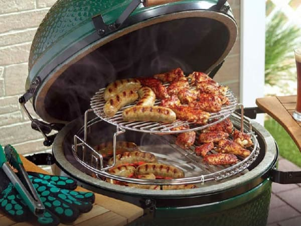 An open Big Green Egg grill filled with seared bratwurst sausages and barbeque glazed chicken wings. Big Green Egg High Heat BBQ gloves sit nearby.