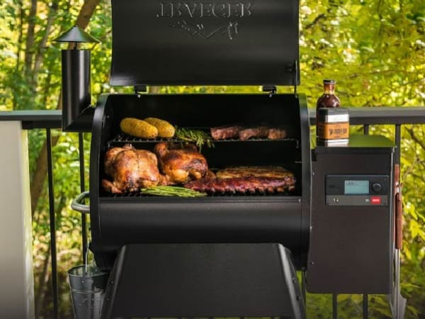A black Traeger pellet grill, brimming with smoked turkey, seared corn on the cob, perfectly cooked steaks, juicy-looking ribs, and fresh asparagus.