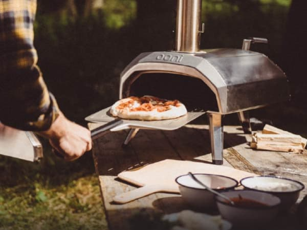 A person uses a pizza peel to slide a personal-sized pizza into an Ooni pizza oven. This portable Ooni oven is set up on a picnic table in a wooded area.