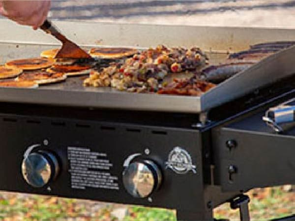 A person flips pancakes on a propane-powered griddle in a grassy area. Also on the grill are hash browns, sausages, and bacon, but there's still plenty of room