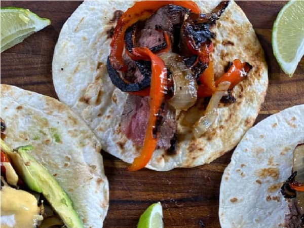 A flour tortilla topped with juicy marinated flank steak, smoked red pepper, and caramelized onions