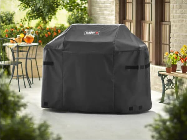A large, covered grill sits outside on a patio. The grill cover has the word Weber printed on it.