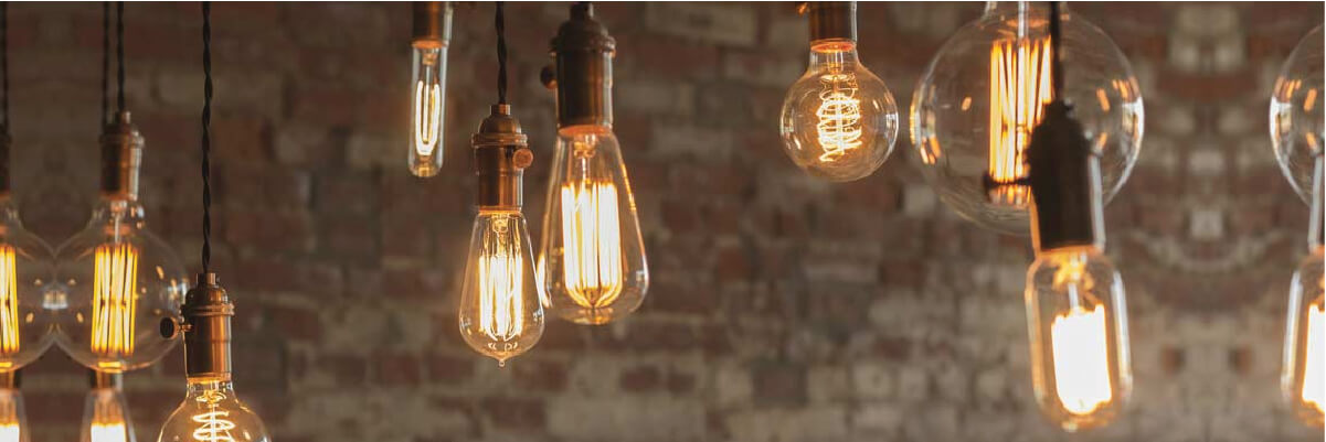 An assortment of bare lightbulbs hanging in front of an exposed brick wall.