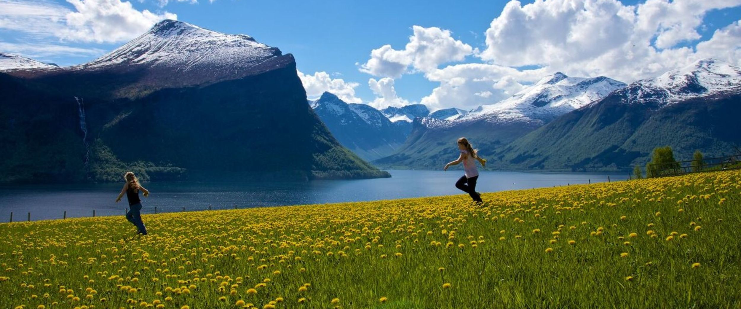 Girls playing in a flowery meadow. Photo: Øyvind Klungnes Heen, visitnorway.com