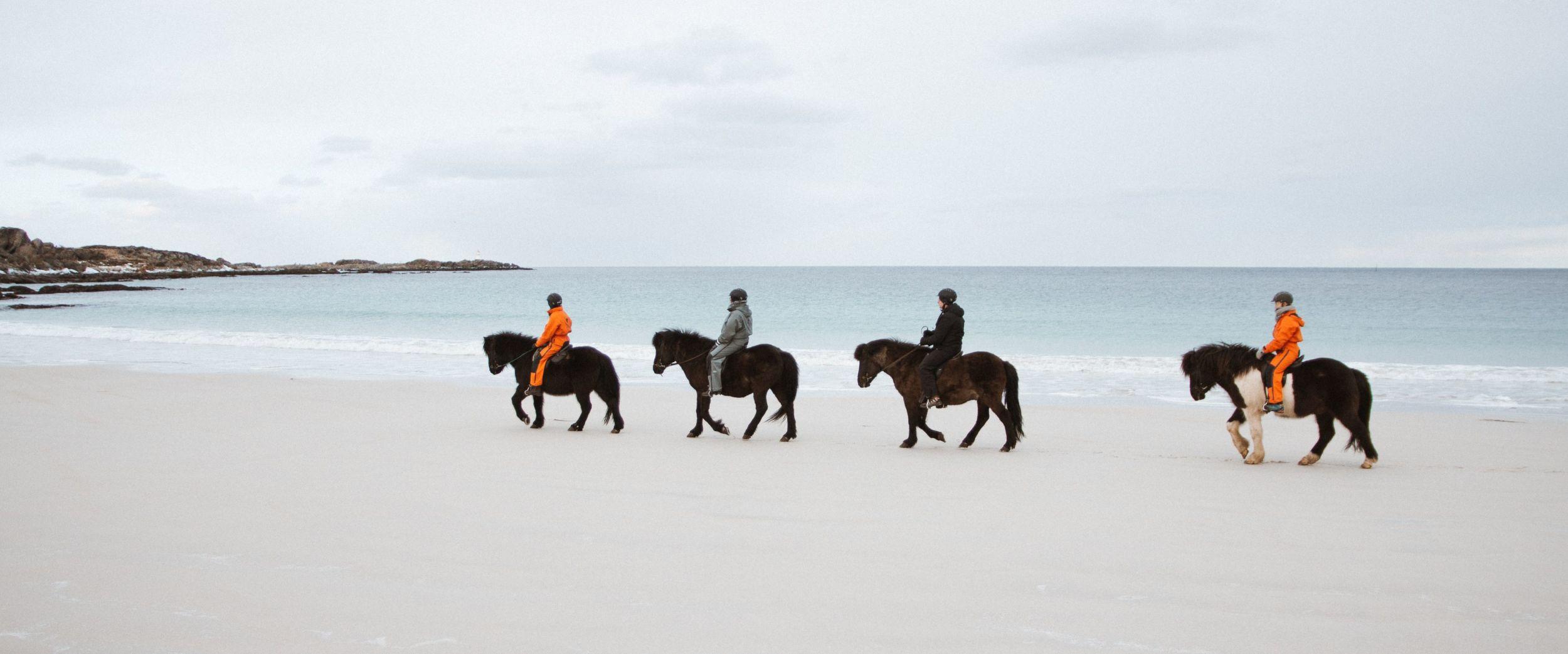 Folk som rir på kvit sandstrand i Lofoten om vinteren