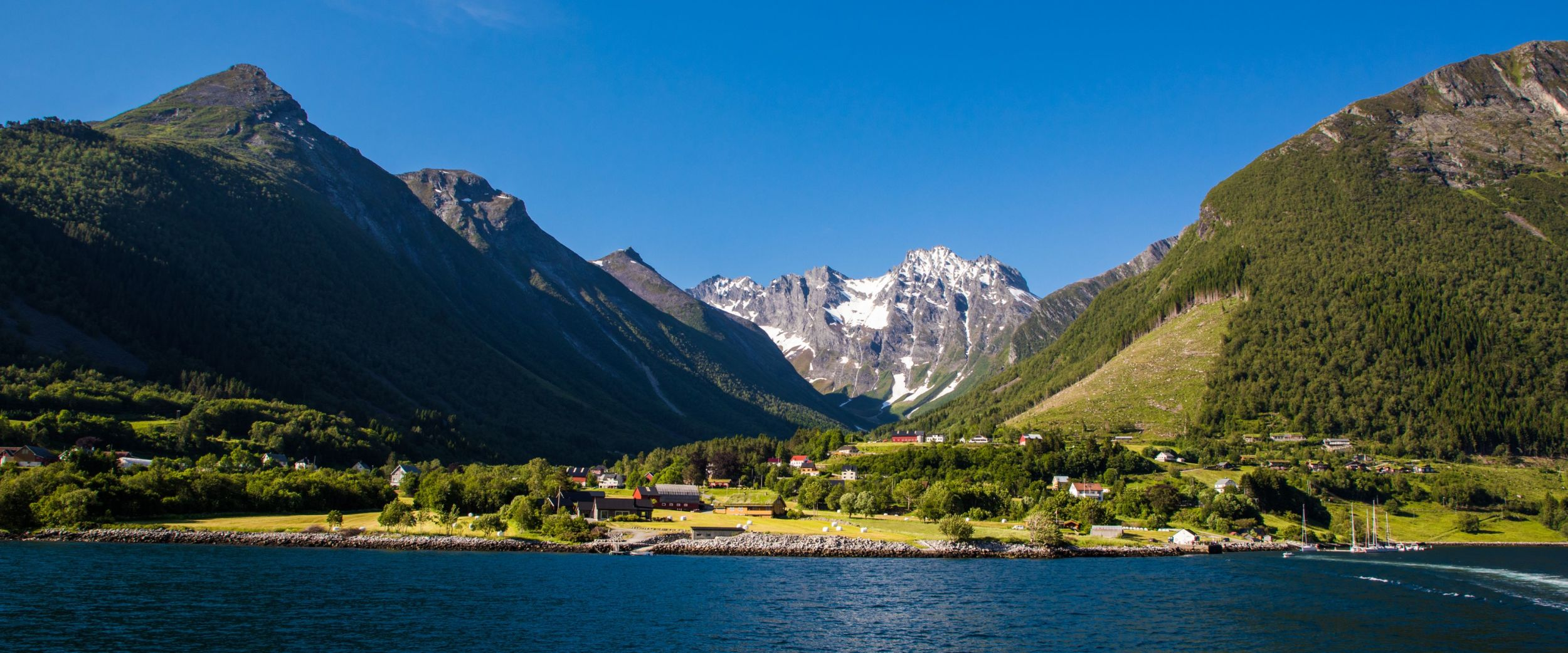 A small hamlet under high mountains in Hjørundfjorden: Photo: AdobeStock