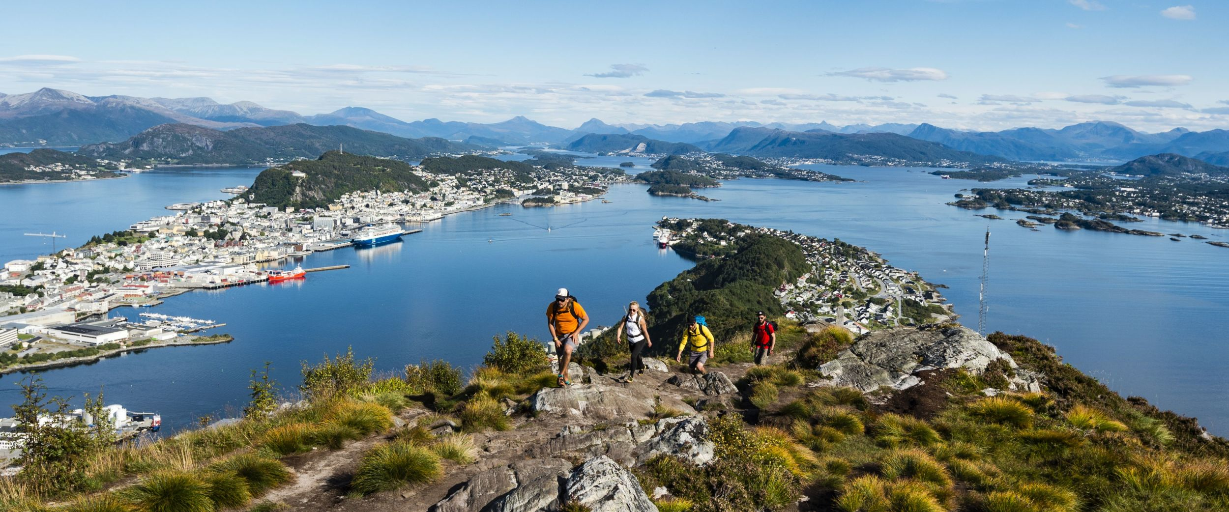 People on a hike to Sukkertoppen with view to Ålesund and the Borgundfjord.