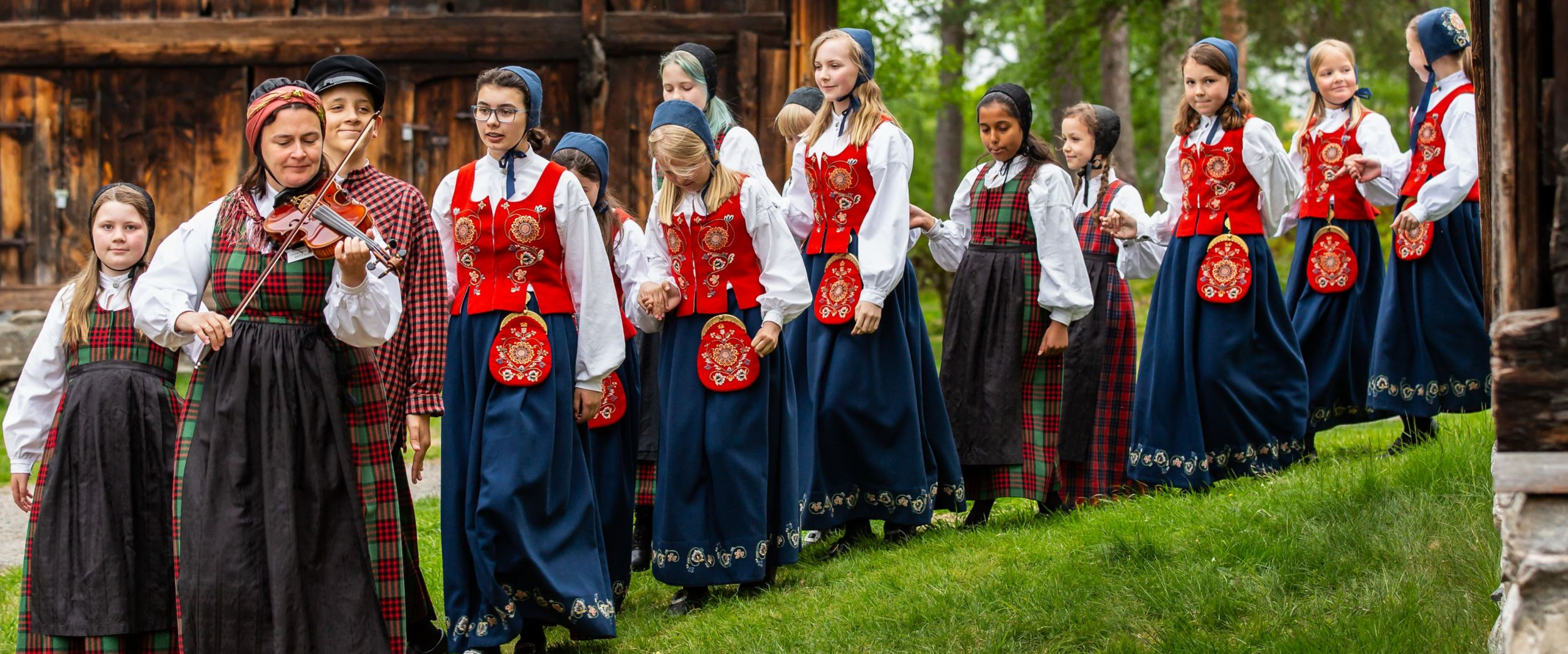 Leikarring at Romsdalsmuseet, woman playing a fiddle and girls in the Norwegian traditional costume Bunad.