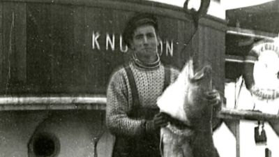 Per as a young man holding up a big fish he has cought