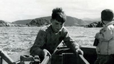 Black and white photo of Per on a boat as a young boy.