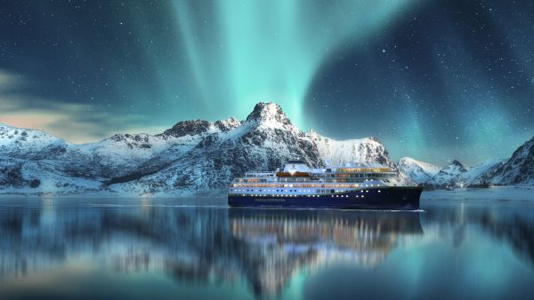 Havila ship in Lofoten with the beautiful Northern Lights dancing in the night sky.
