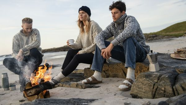 People by the campfire in nitted woolsweaters from Devold. Photo: Devold.