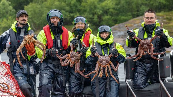 Happy people in a rib holding king crabs.