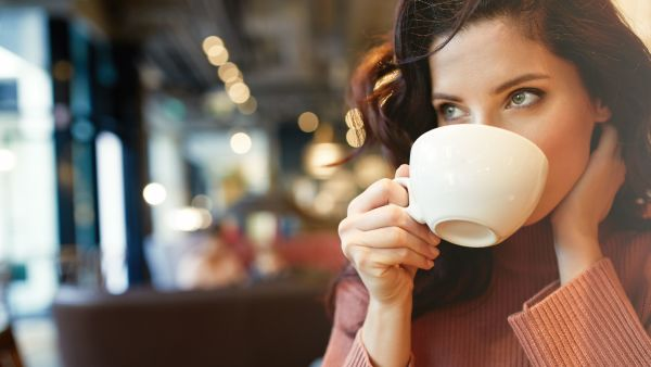 Woman drinking coffee from a white cup.