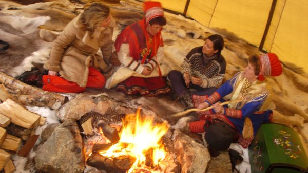 People around the campfire in a sami telt dressed in traditional sami costumes. Photo: Trym Ivar Bergsmo, nordnorge.com