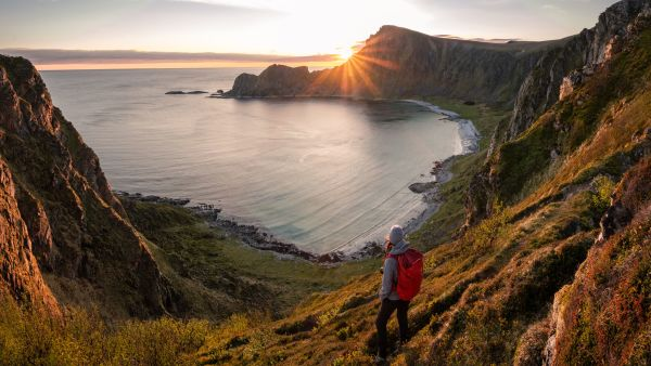 A woman hiking during midnight sun. Active vacation in Norway. Located on Andøya island in Vesterålen north of Norway. Sunset and backpack girl.