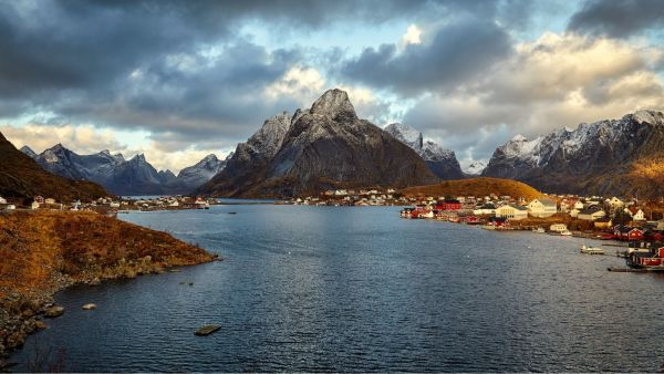 The fishing village Reine with the Lofoten archipelago in the background seen in the sunset with a cloudy sky.