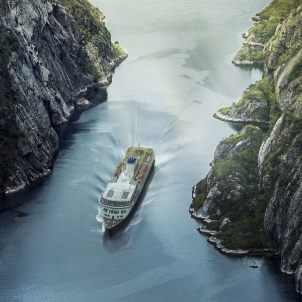 Havila ship sailing through narrow fjord with steep stony sides and some green vegetation.