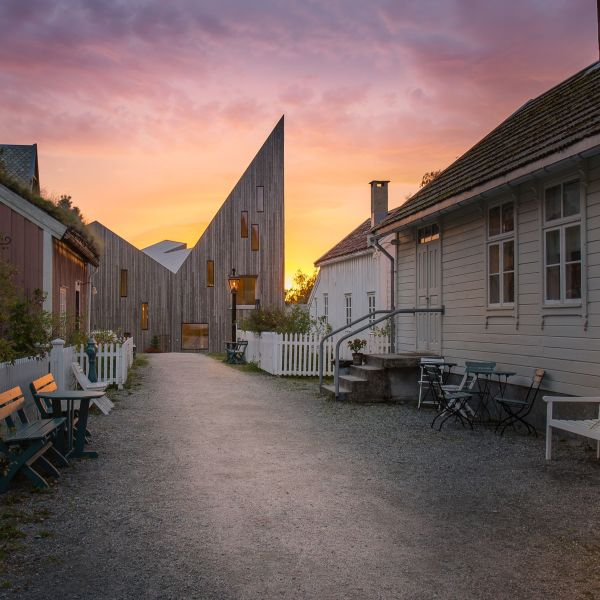 Street in Romsdalsmuseet with traditional houses and modern museum building in sunset.