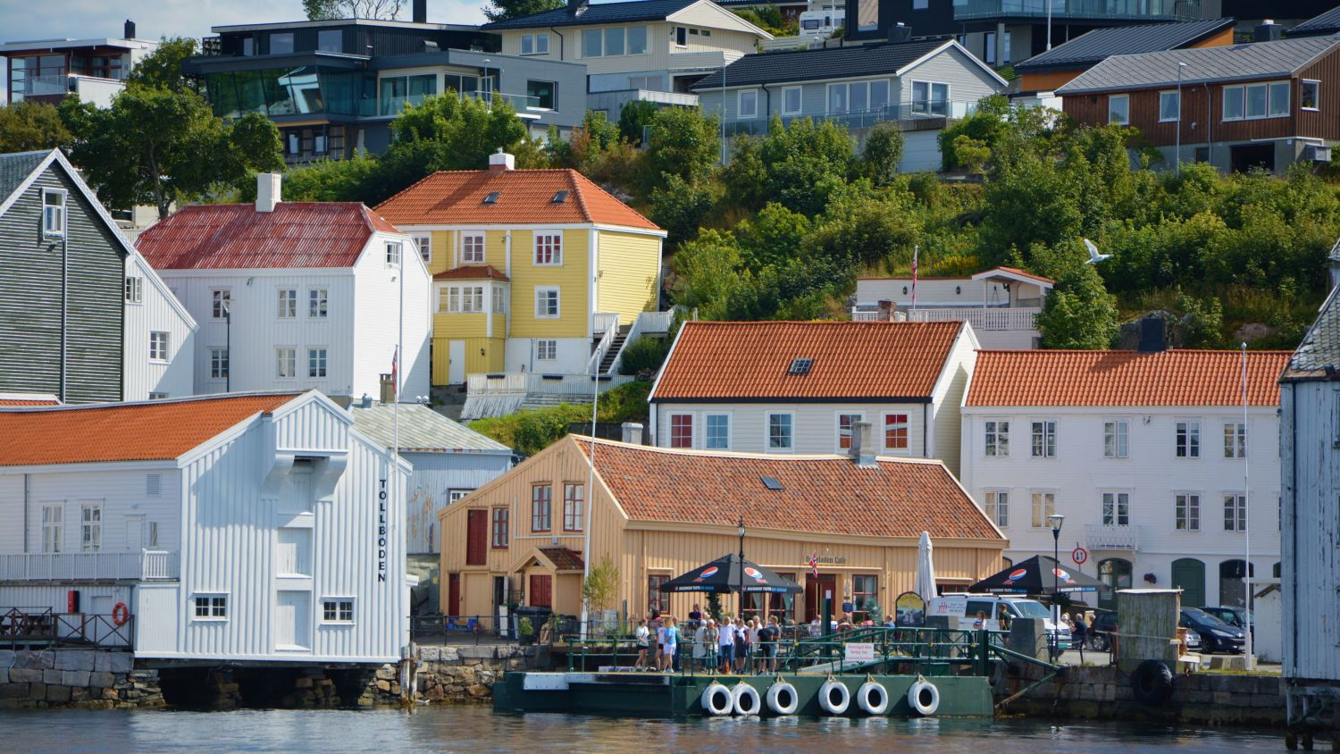 Old, white wooden houses and an outdoor cafe on a sunny summerday in Kristiansund