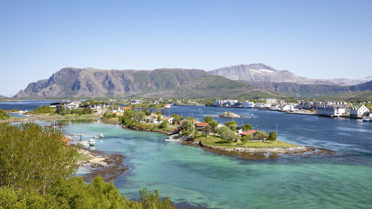 Islands off Brønnøysund with clear green water on a sunny day.