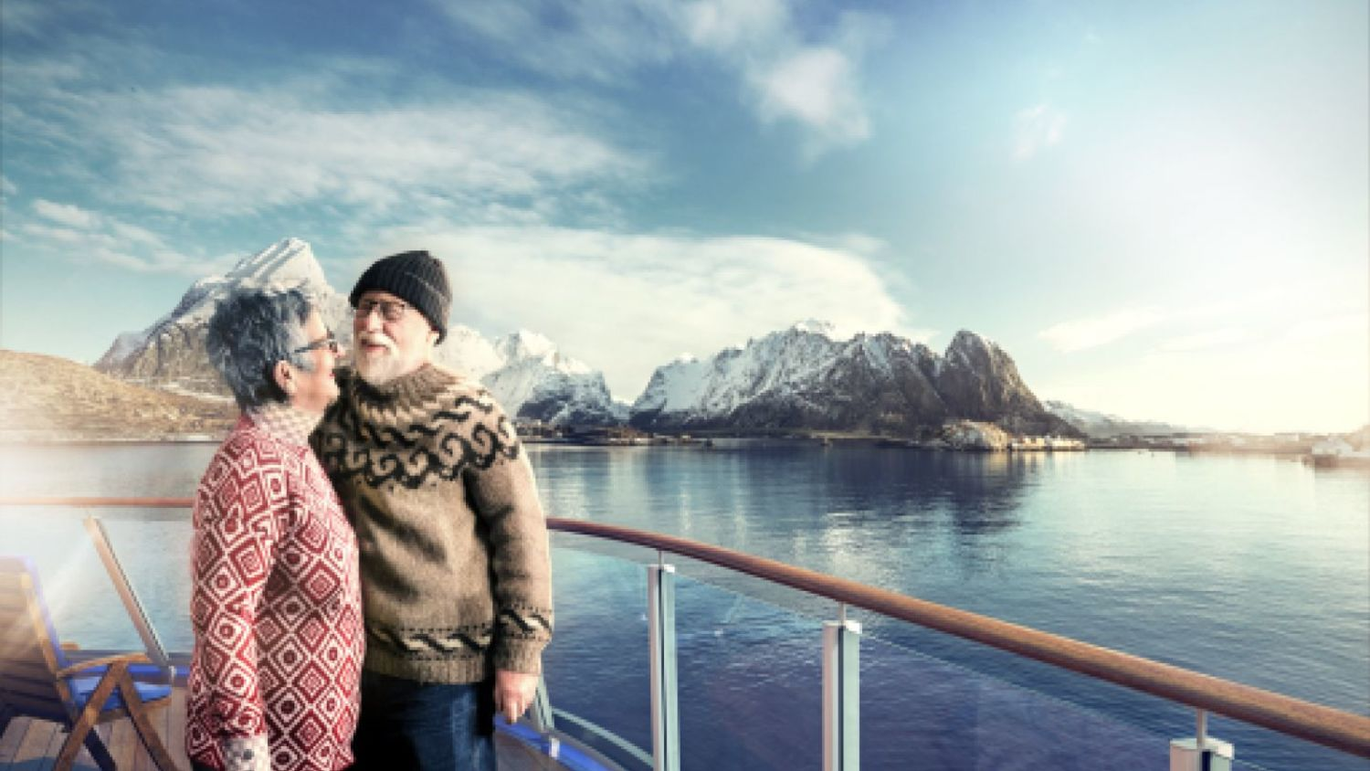 Elderly couple on deck of a Havila ship with Lofoten in the background.