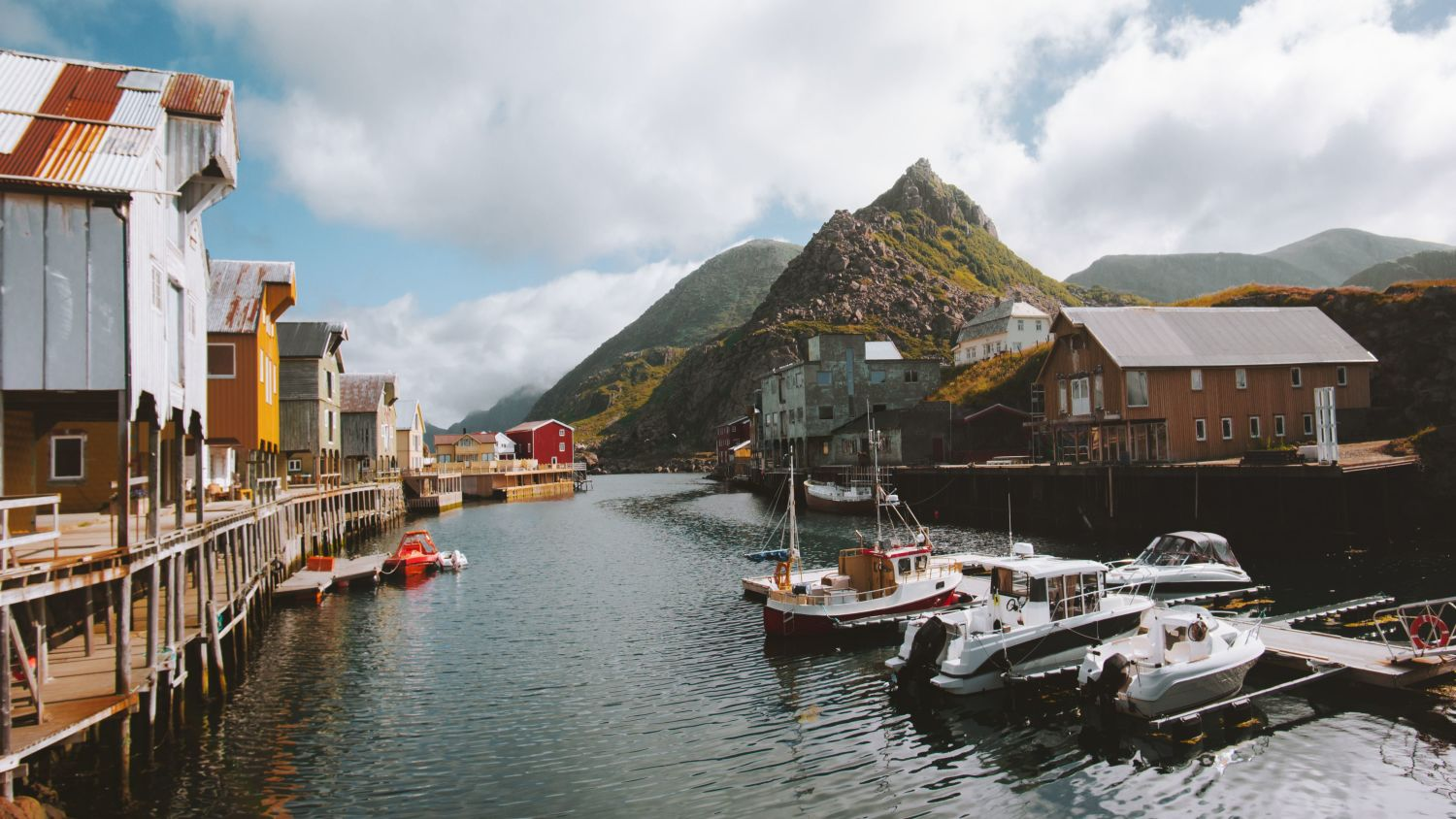 Nyksund fishing village in Vesterålen with boathouses, and boats in front of green mountain.