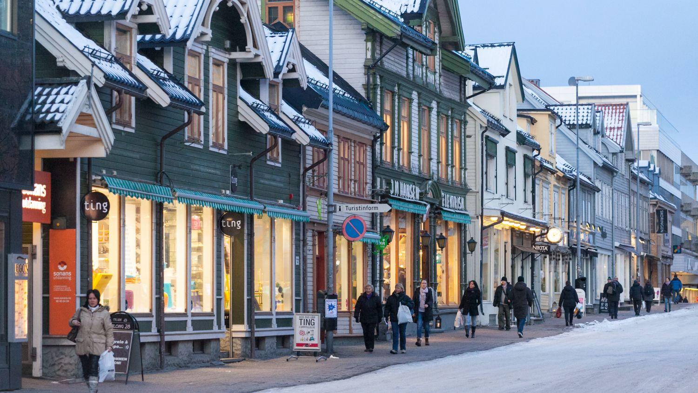 Folk i vinterleg gate med trehus i Tromsø