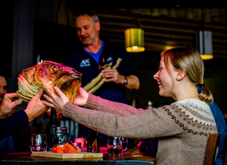 Smak av Lofoten og jente som helsar på eit tørka torskehovud