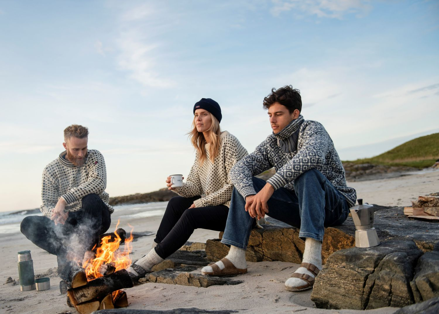 Young people at the beach with a bonfire, dressed in knitted sweaters. Photo: Devold.no