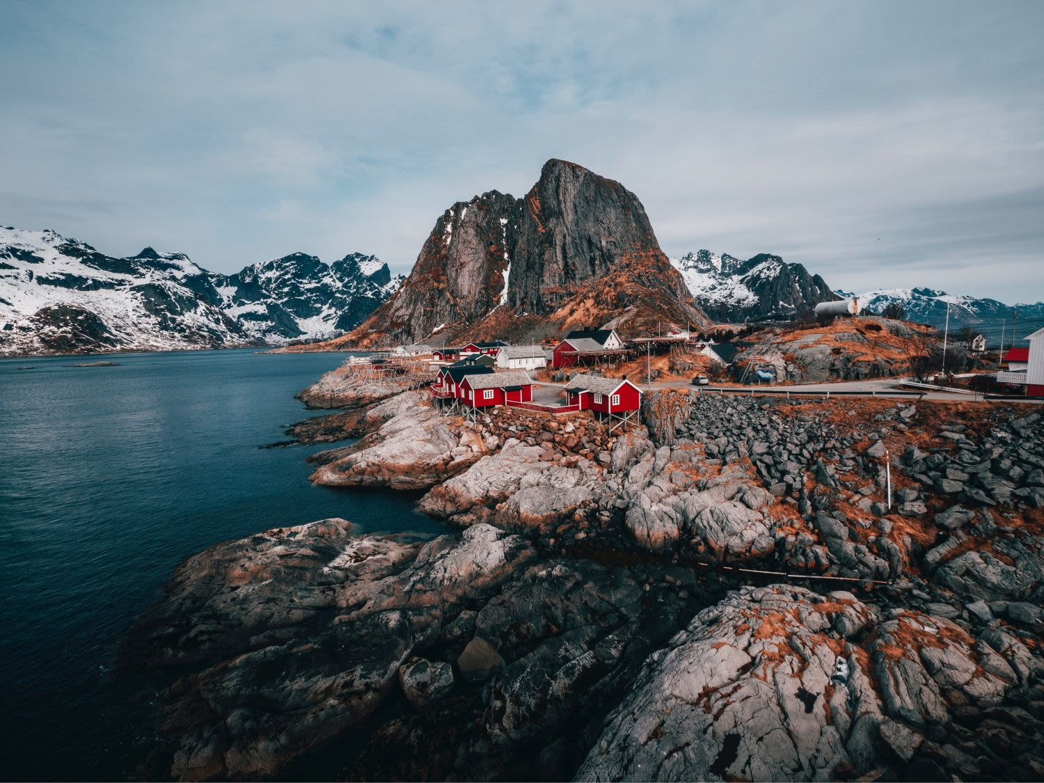 Red houses on rocky shoreline with majestic mountains in the background.
