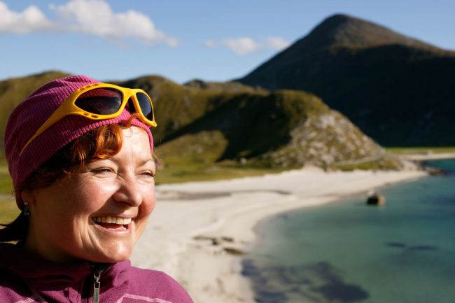 A smiling woman at Hauklandstranda beach in Lofoten. Photo: Nils Erik Bjørholt, visitnorway.com