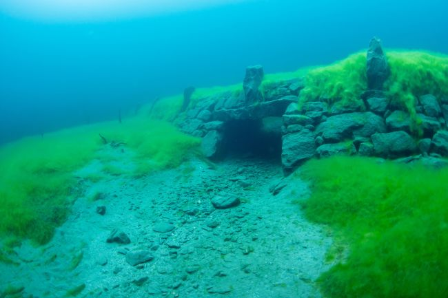 Diving in Lyngstøylvatnet where small farms where submerged. Photo: Adobe Stock