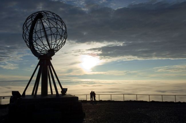 People watching the midnight sun next to the globe at the North Cape. Photo: Johan Wildhagen, visitnorway.com