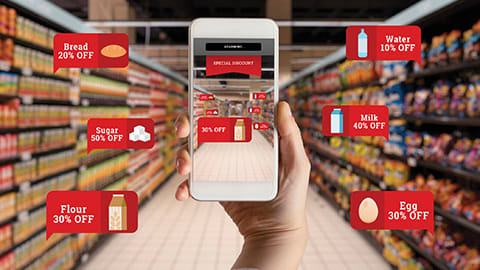 hand holding a shopping app with grocery store aisle in background