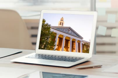 laptop open with screen showing HBS Baker Library