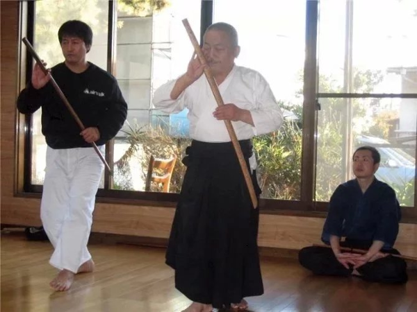 Two martial artists draw their swords as another one looks on