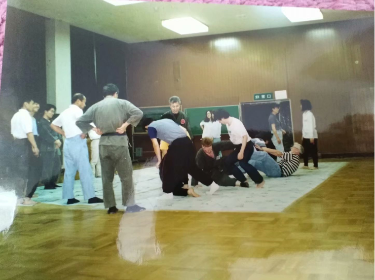 A dozen martial arts students roll around on the floor, as others look on.