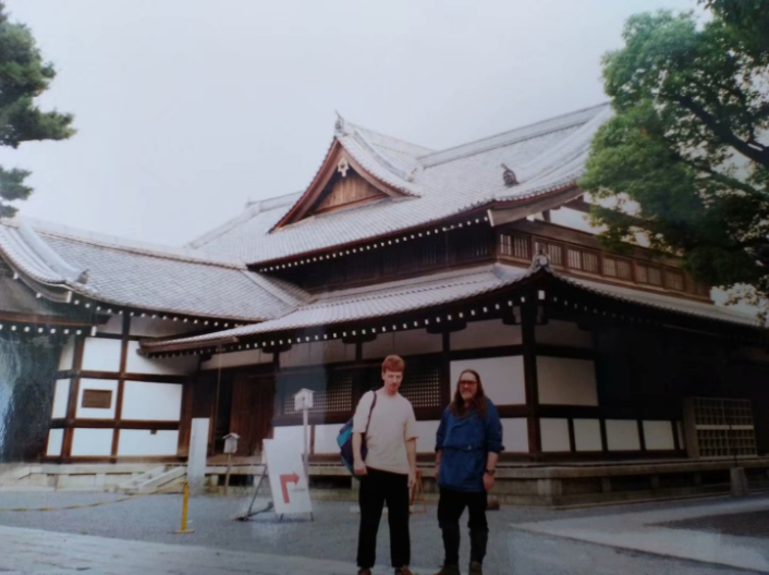 Two men stand in front of a large, traditional Japanese building