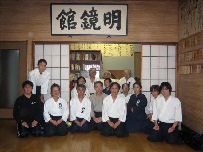 A group of Japanese martial artists sit together inside a dojo