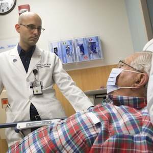 Ephraim Tsalik, MD, PhD, at Duke Health assesses a patient for respiratory symptoms.