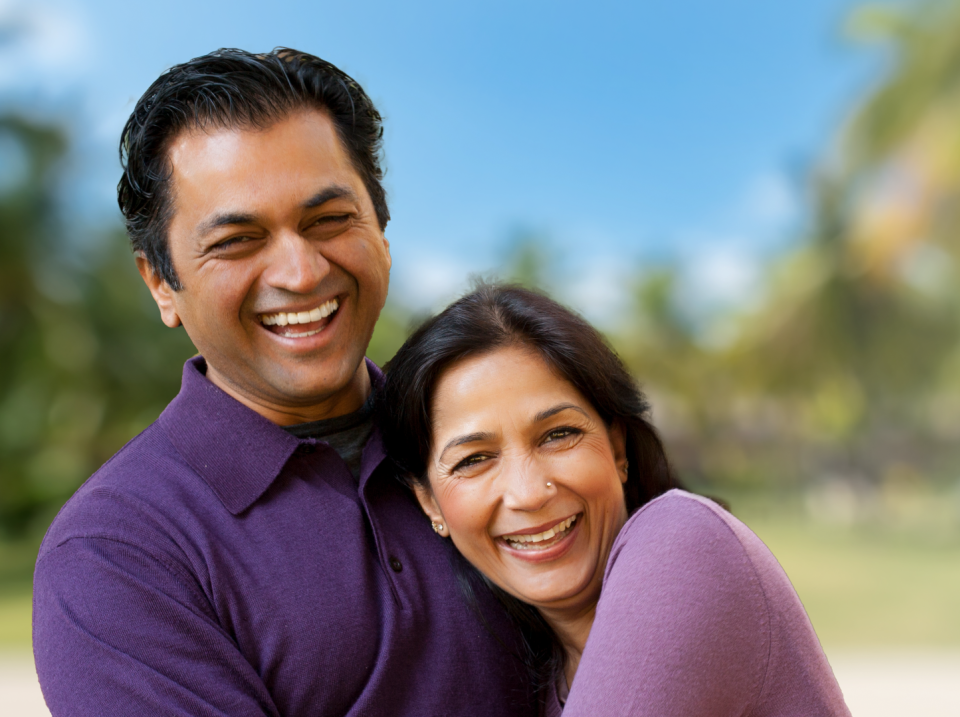 smiling couple with palm trees in background