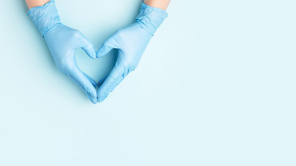 Photo of gloved hands in a heart shape