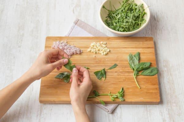 Snipper de sjalot en snijd of pers de knoflook fijn en scheur de basilicum en rucola