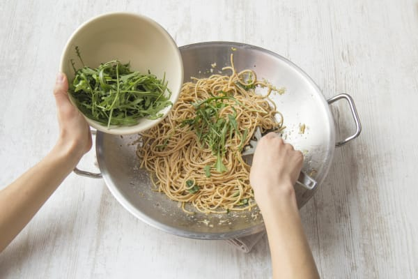 Voeg het grootste deel van de rucola toe aan de spaghetti