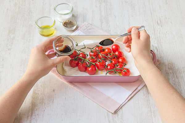 Besprenkel de tomaten met zwarte balsamicoazijn.