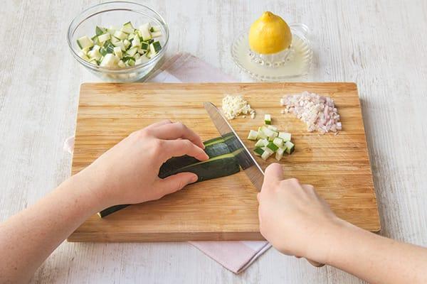 Snijd de knoflook, sjalot en courgette. Rasp de citroen en pers het sap uit.