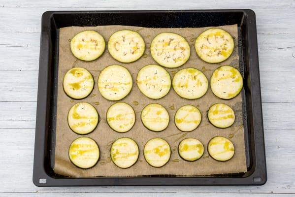Verdeel de aubergine op een bakplaat met bakpapier en wrijf in met de helft van de olijfolie, peper en zout.
